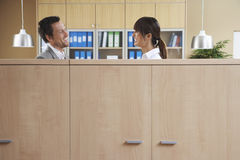 Office Couple Talking Behind Cubicle Royalty Free Stock Image