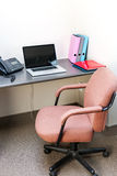 Office cubicle with laptop computer. Workstation in office with swivel chair desk and laptop computer Royalty Free Stock Photo