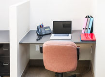 Office cubicle with laptop computer. Workstation in office with swivel chair desk and laptop computer Royalty Free Stock Photography