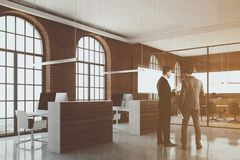 Office cubicles in brick office corner, people Royalty Free Stock Photo