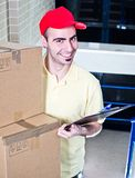 Office delivery. Young smiling man working as delivery courier - photo on office stairs Stock Photos