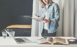 Office design studio, young businesswoman in denim shirt standing near desktop and leafing through catalog. Stock Photography