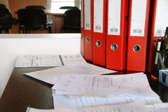 Office desk. With red folders and various documents Royalty Free Stock Photography
