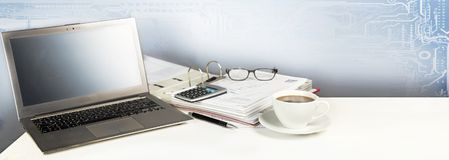 Office desk with alaptop computer, a big folder and a cup of coffee, digital business concept, panoramic banner format stock photos