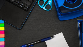 Office desk - all items in blue. Blue items on an office desk. Space for advertisement´s and notes. black leaded desk with blue scissor, stapler, puncher Royalty Free Stock Image