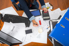 Office desk as seen from above, papers spread out, calculators, computer keyboards, pens and arm writing Royalty Free Stock Image