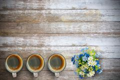 Office desk-Black hot coffee in a green cup on the old wooden ta. Office desk-Black hot coffee in a cup and flower on the old wooden table background.Top view Stock Photos