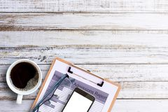 Office desk-Black hot coffee in a white cup and glasses on old w. Office desk- cup of coffee, healthcare admissions report ,smartphone and glasses on old wooden Royalty Free Stock Photography