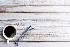 Office desk-Black hot coffee in a white cup and glasses on old w. Ooden table background.Top view with copy space design for image or text. Business and Royalty Free Stock Photo