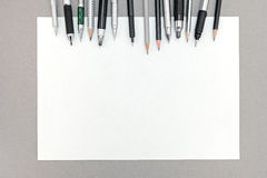 Office desk with blank sheet of paper and various drawing tools Stock Images