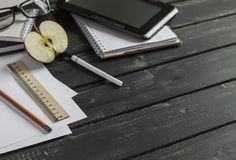 Office desk with business objects - open notebook, tablet computer, glasses, ruler, pencil, pen. Royalty Free Stock Photography
