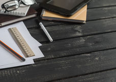 Office desk with business objects - open notebook, tablet computer, glasses, ruler, pencil, pen. Free space for text. Royalty Free Stock Photos