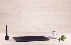 Office desk closeup with white brick wall Royalty Free Stock Images