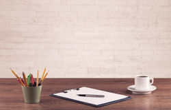 Office desk closeup with white brick wall Royalty Free Stock Photo