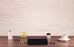 Office desk closeup with white brick wall Royalty Free Stock Image