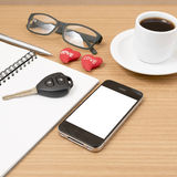 Office desk : coffee and phone with car key,eyeglasses,notepad,h Royalty Free Stock Image