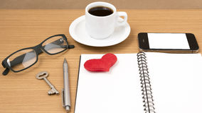 Office desk : coffee and phone with key,eyeglasses,notepad,heart Royalty Free Stock Image