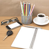 Office desk : coffee and phone with key,eyeglasses,notepad,penci Royalty Free Stock Image