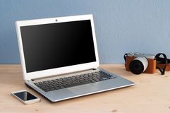 Office Desk with Computer Notebook, Cell Phone and camera Stock Photo