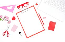 Office desk with a computer, a red notebook, scissors, clipboard. Red glasses and a pink flower. Flat lay with free space for text Royalty Free Stock Photo