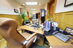 Office with desk, computer, telephones and folders. With papers, ginger leather armchair Royalty Free Stock Images