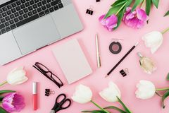 Office desk with computer, tulip flowers, cosmetics, glasses, diary and pen on pink background. Flat lay. Top view. Stock Images
