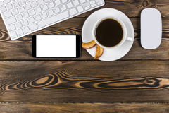 Office desk with copy space. Digital devices wireless keyboard, mouse and smartphone with empty screen on dark wooden table Stock Image