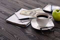 On the office desk cup of coffee, notepad and dollars Stock Photography