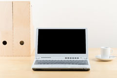 Office desk with cup, folders and laptop Royalty Free Stock Photos