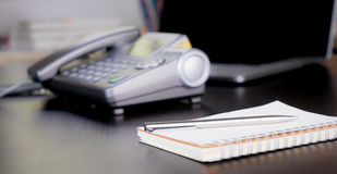 Office desk with dial phone and notebook Stock Image