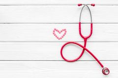 Stethoscope and heart for diagnostic and cure of heart disease on white desk background top view mockup. Office desk for doctor. Health care concept. Stethoscope royalty free stock images