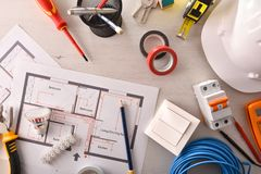 Office desk of electrical engineer with installation project and tools royalty free stock image