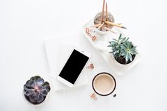Office desk flat lay with coffe, smartphone and succulents, clea. White home office desk flat lay with coffe, smartphone and succulents, clean stylish bloggers Royalty Free Stock Photos