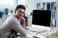 At office desk. Handsome Indian businessman sitting at modern office desk Stock Photography