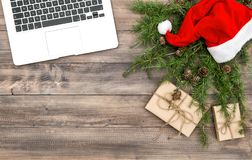 Office desk laptop Christmas decoration red hat gifts stock photos