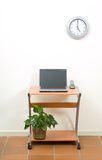 Office desk, laptop and clock Stock Image