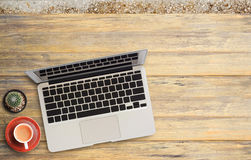 Office desk with laptop computer and coffee cup on wooden. Stock Image