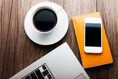 Office desk with laptop computer, planner, mobile smartphone. And coffee cup Royalty Free Stock Photos
