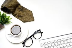 Modern white office desk top table with a cup of coffee, Necktie  and other supplies. Top view with copy space stock images