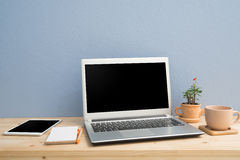 Office desk with laptop, Note paper, Euphorbia milii flower on terracotta flower pot and blank screen tablet. View from front wood table Royalty Free Stock Images