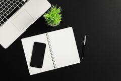 Office Desk with Laptop and Notebook. Office table desk with, laptop smart phone and notebook on black background. Top view Royalty Free Stock Photo