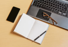 Office desk with laptop, opened planner and smartphone. Top view Stock Images