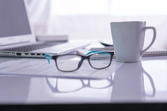 Office desk with laptop, pens, glasses Stock Photography