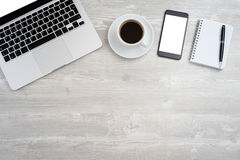 Office desk with laptop. Smartphone, cup of coffee. Top view with copy space Royalty Free Stock Photo