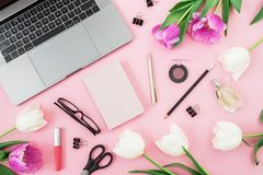 Office desk with laptop, tulip flowers, cosmetics, glasses, diary and pen on pink background. Flat lay. Top view. Office desk with laptop, tulip flowers royalty free stock images