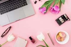 Office desk with laptop, tulip flowers, cosmetics, glasses, pen and cookies on pink background. Flat lay. Top view. Freelance or b. Usiness concept stock photography
