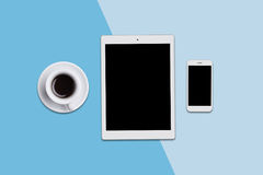 Office desk with modern tablet, smart phone and cup of coffee. View from above of modern gadgets lying on blue background. Modern Stock Photography