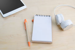 Office desk with Note Paper, Notepad screen and earphone . View Royalty Free Stock Images