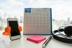 Office desk with note to remind on calendar with smartphone. Office desk with note to remind on calendar, smartphone and headphone Stock Image