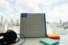 Office desk with note to remind on December calendar. Office desk with note to remind on calendar and headphone Stock Photography
